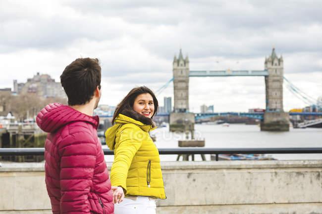 Великобритания, Лондон, молодая пара, идущая рука об руку по мосту через Темзу — стоковое фото