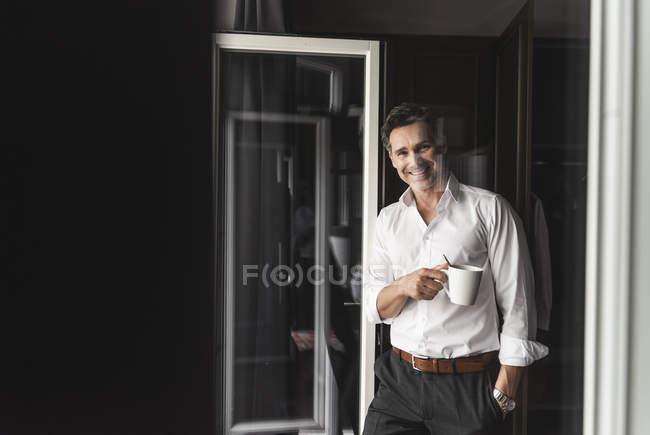 Uomo d'affari sorridente con una tazza di caffè in piedi alla finestra a casa — Foto stock