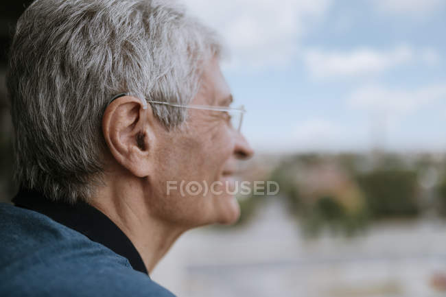 Smiling senior man with hearing aid outdoors — Stock Photo