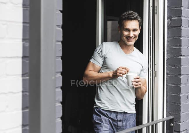 Porträt eines lächelnden Mannes im Pyjama zu Hause mit einer Tasse Kaffee an der Balkontür — Stockfoto