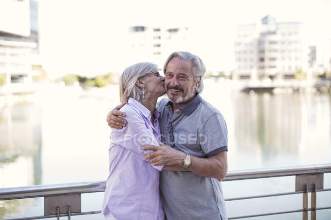 Senior couple taking a city break, kissing and embracing — Stock Photo