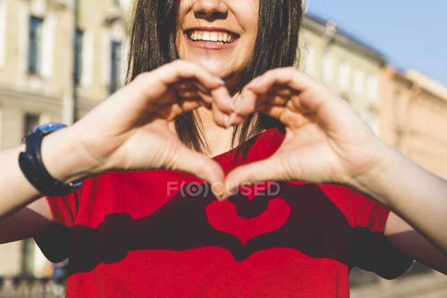 Woman's hands shaping heart, shadow on red t-shirt — Stock Photo