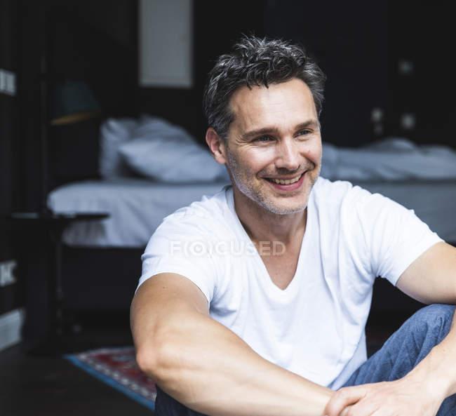 Homem de sorriso no pijama em casa que senta-se para baixo — Fotografia de Stock