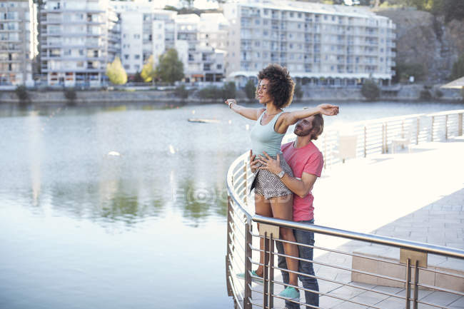 Женщина балансирует на перилах с закрытыми глазами, пока мужчина держит ее — стоковое фото