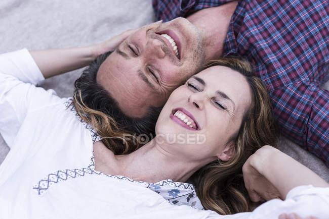 Heureux couple affectueux couché sur une couverture — Photo de stock