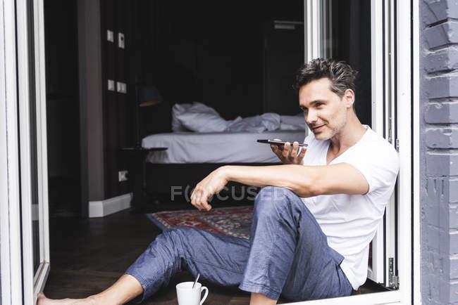 Uomo in pigiama a casa seduto alla finestra francese utilizzando lo smartphone — Foto stock