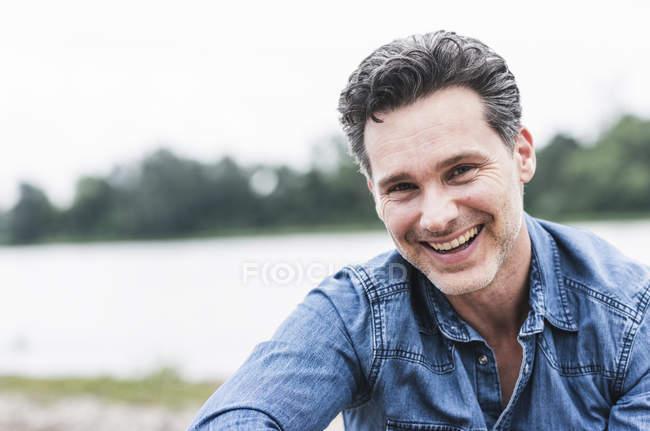Портрет щасливого чоловіка на березі річки — стокове фото