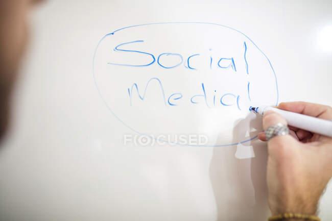 Close-up of man writing on whiteboard — Stock Photo