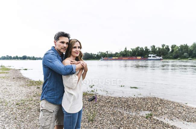Ласковая пара на берегу реки — стоковое фото