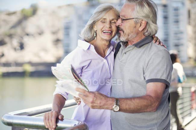 Старшая пара отдыхает в городе, держит карту — стоковое фото