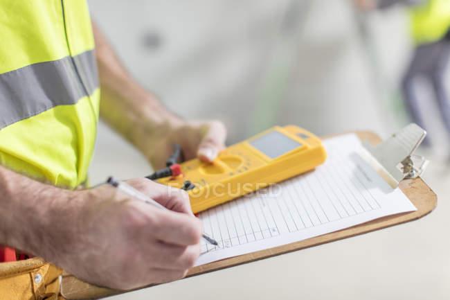 Nahaufnahme eines Elektrikers, der Notizen macht — Stockfoto