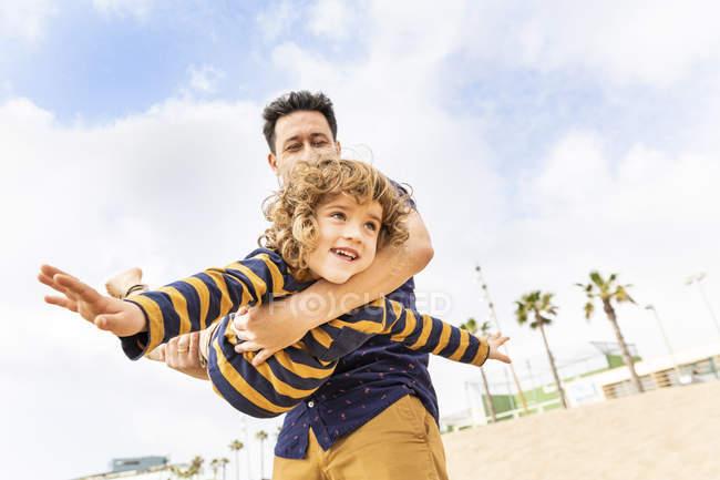 Spain, Barcelona, pai e filho que jogam na praia — Fotografia de Stock