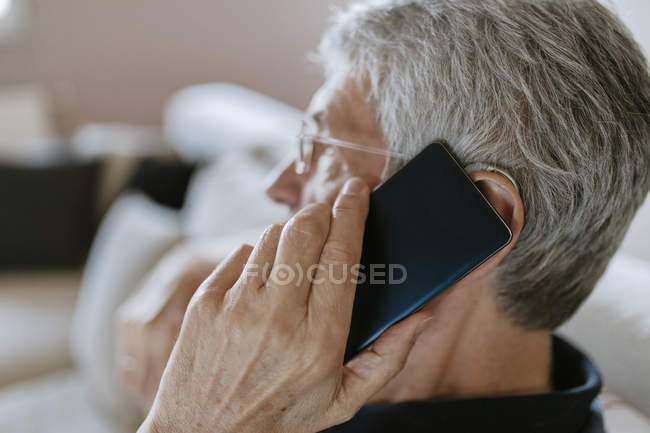 Senior man with hearing aid on cell phone — Stock Photo