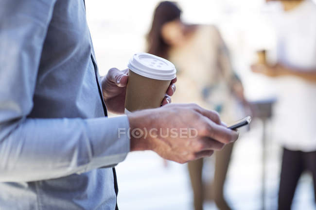 Hand of a man holding cup of coffee, using smartphone — Stock Photo
