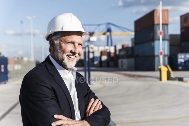 Бизнесмен в грузовой гавани, в защитном шлеме, со скрещенными руками — стоковое фото