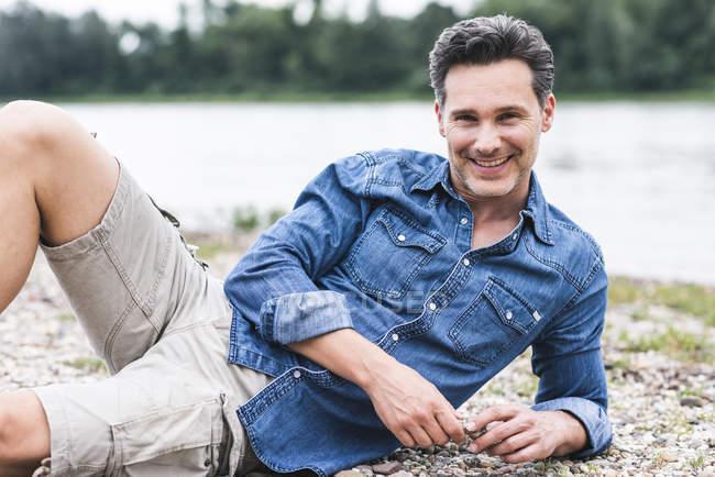 Retrato de homem sorridente relaxando à beira do rio — Fotografia de Stock