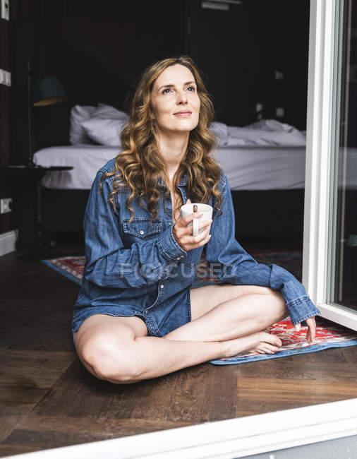 Donna sorridente in camicia di jeans a casa con tazza di caffè seduta alla finestra — Foto stock