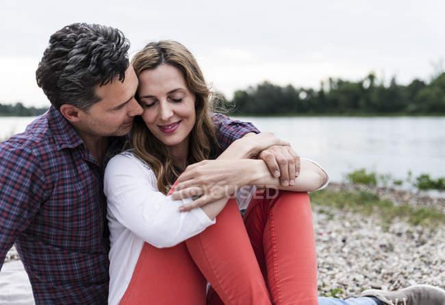 Ласковая счастливая пара, сидящая на берегу реки — стоковое фото