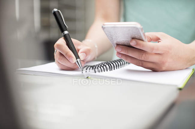 Mulher escrevendo notas no diário, segurando smartphone — Fotografia de Stock
