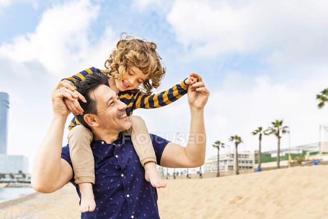 Spain, Barcelona, father with son on the beach giving a piggyback ride — Stock Photo