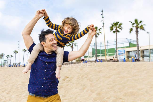 España, Barcelona, padre con hijo en la playa dando un paseo a cuestas - foto de stock