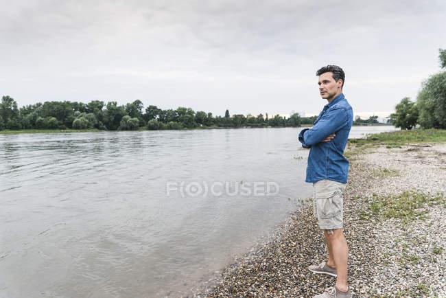 Uomo in piedi sul lungofiume guardando fuori — Foto stock