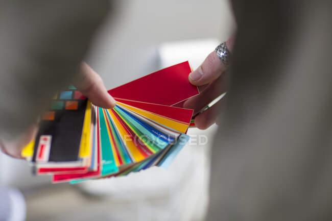 Primer plano del hombre sosteniendo muestras de color en la oficina - foto de stock