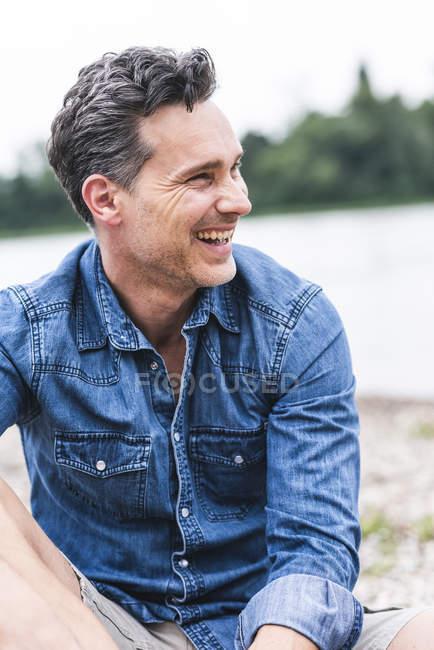 Чоловік сміється на березі річки дивлячись у бік — стокове фото