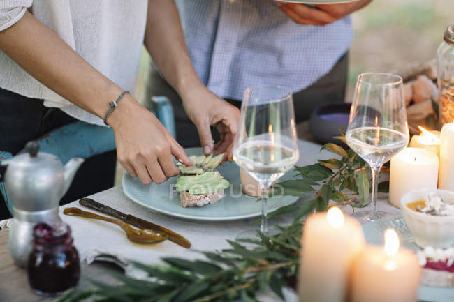 Close-up of couple preparing a romantic candlelight meal outdoors — Stock Photo