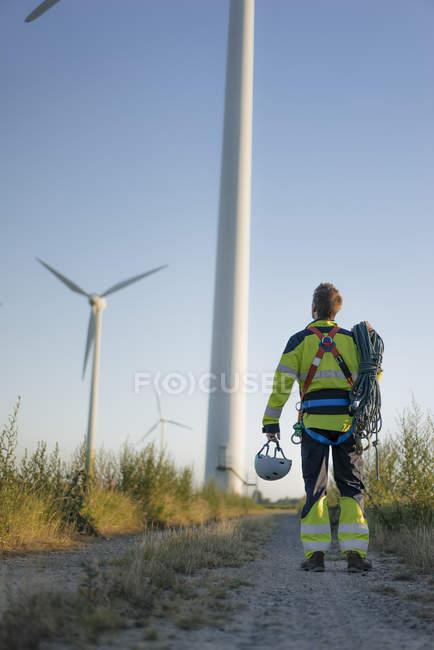 Техник, стоящий на полевой дорожке на ветропарке с альпинистского снаряжением — стоковое фото