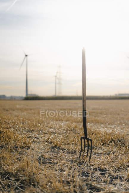 Pitchfork в поле в сельской местности с ветровыми турбинами в фоновом режиме — стоковое фото