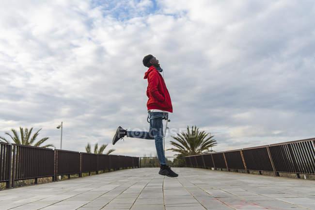 Giovane uomo nero in piedi all'aperto, saltando per la gioia — Foto stock