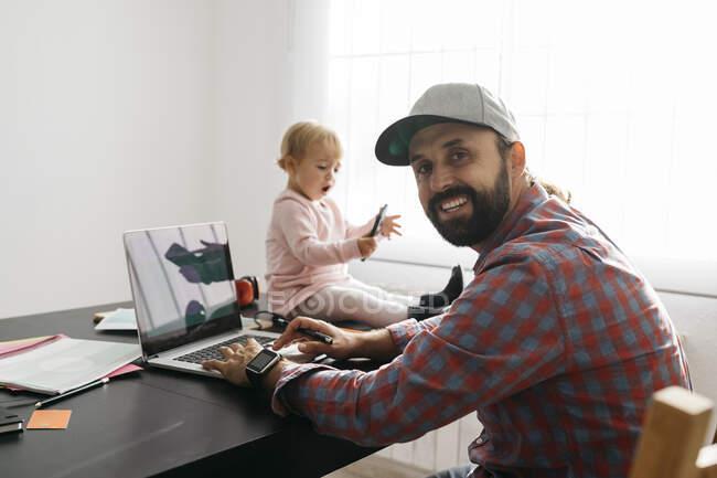 Vater arbeitet von zu Hause aus, benutzt Laptop, während sein Messgerät auf dem Schreibtisch sitzt und spielt — Stockfoto