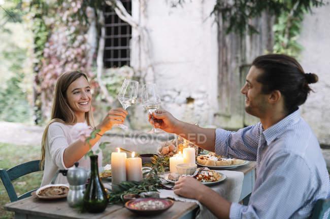 Pareja teniendo una cena romántica a la luz de las velas al lado de una casa de campo y tintineo copas de vino - foto de stock
