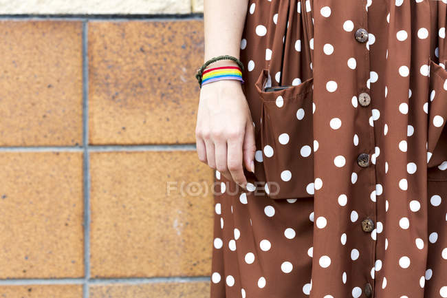 Young woman wearing brown dress with white polka dots and wristband with prismatic colours, partial view — Stock Photo