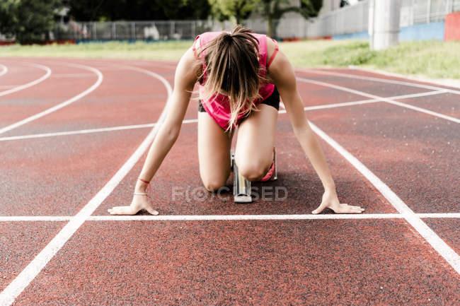Юный бегун в стартовой позиции на ипподроме — стоковое фото