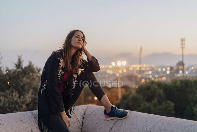 Spain, Barcelona, Montjuic, young woman sitting on a wall at dusk with city lights in background — Stock Photo