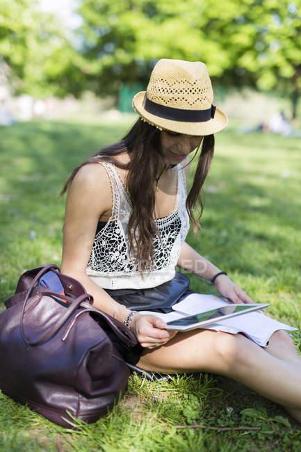 Junge Studentin sitzt auf einer Wiese im Park und nutzt digitales Tablet — Stockfoto