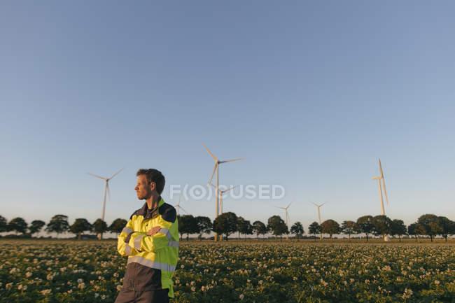 Інженер стоїть на полі на вітровій фермі. — стокове фото
