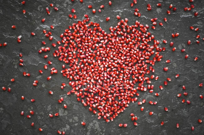 Coração dado forma das sementes da romã na ardósia — Fotografia de Stock