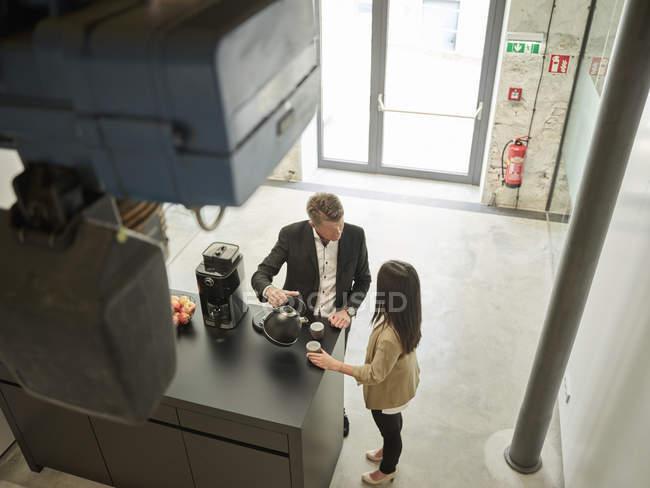 Бизнесмен и предпринимательница во время кофе-брейка в офисе — стоковое фото