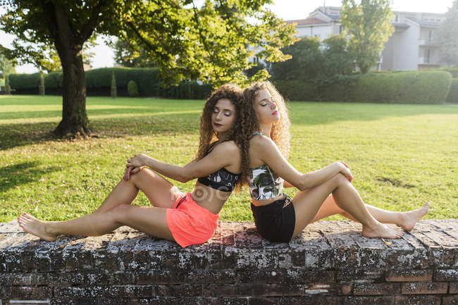 Portrait of twin sisters sitting barefoot back to back on a wall in summer — Stock Photo