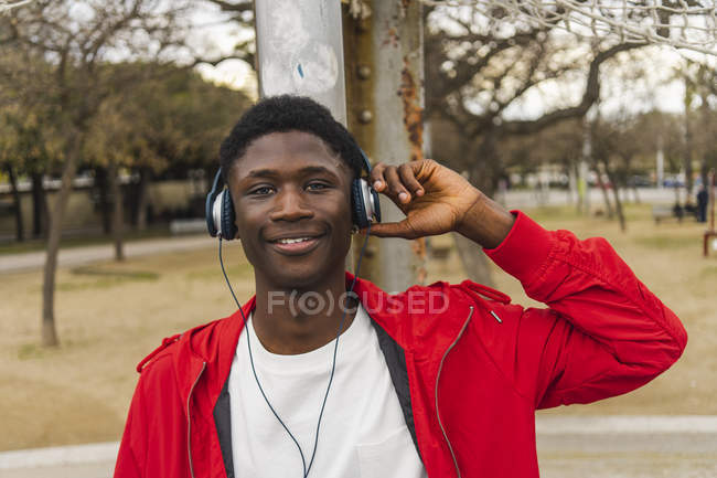 Young black man with headphones, smiling, portrait — Stock Photo
