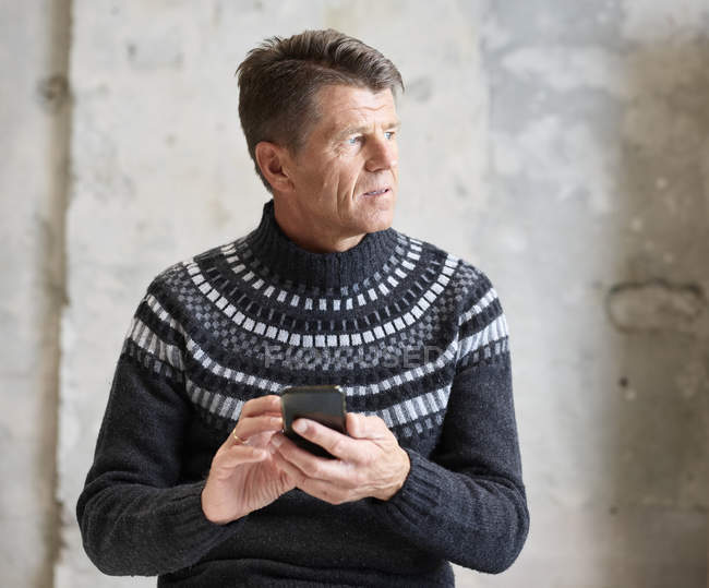 Homme portant un pull-over tenant un téléphone cellulaire — Photo de stock
