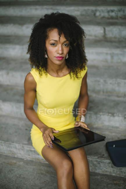 Retrato de mujeres de negocios de moda vestidas en amarillo sentadas en escaleras con tableta digital - foto de stock