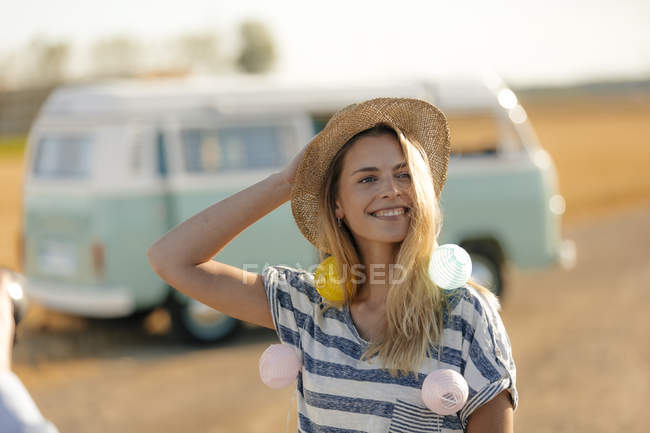 Happy young woman at camper van in rural landscape — Stock Photo