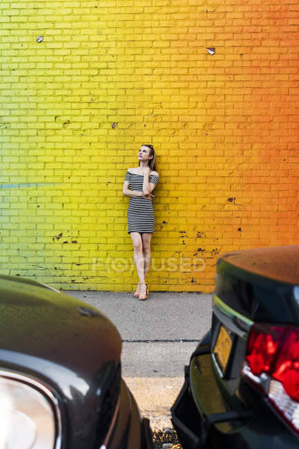 USA, New York, Brooklyn, Dumbo, young woman wearing striped dress and leaning against yellow wall — Stock Photo