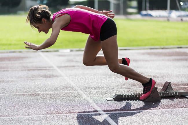 Teenage runner training start on race track — Stock Photo