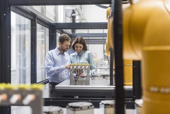 Collègues dans la compagnie de technologie de pointe contrôlant des robots industriels, utilisant la tablette numérique — Photo de stock