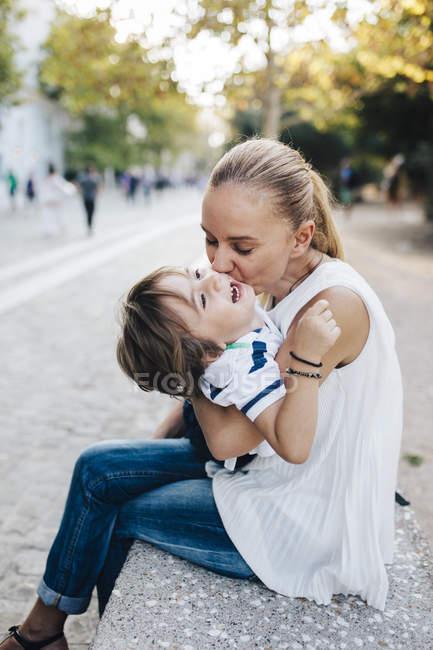 Madre seduta sulla panchina, coccola con suo figlio — Foto stock
